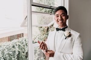 asian groom wearing white tuxedo in a magical city wedding in melbourne photo by black avenue productions