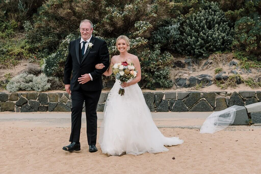 father walking their daughter down the sandy aisle at beach wedding in Brighton Savoy