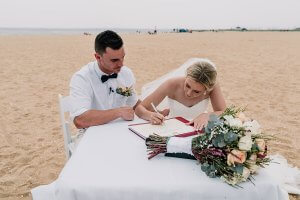 groom and bride signing papers in Brighton Savoy