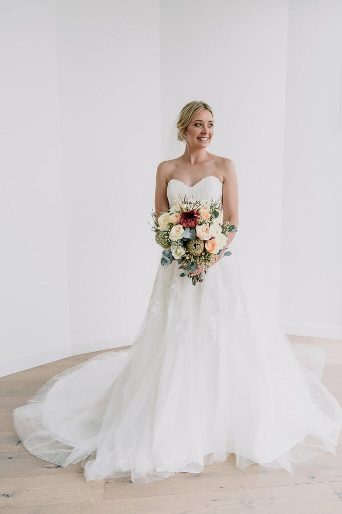 bridal shot with white gown by Luv Bridal and Formal and bouquet shot by award winning wedding photographers Black Avenue Productions