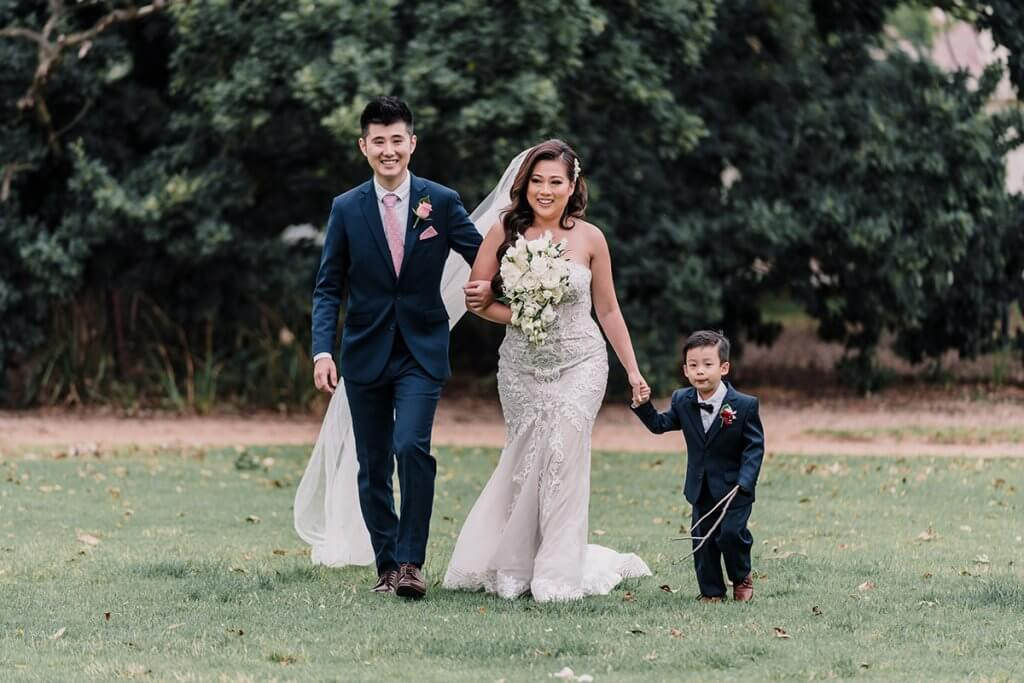 Bride with her brother (left side) and son (right side) walking on the aisle in a garden wedding in Kamesburgh Gardens shot by Black Avenue Productions