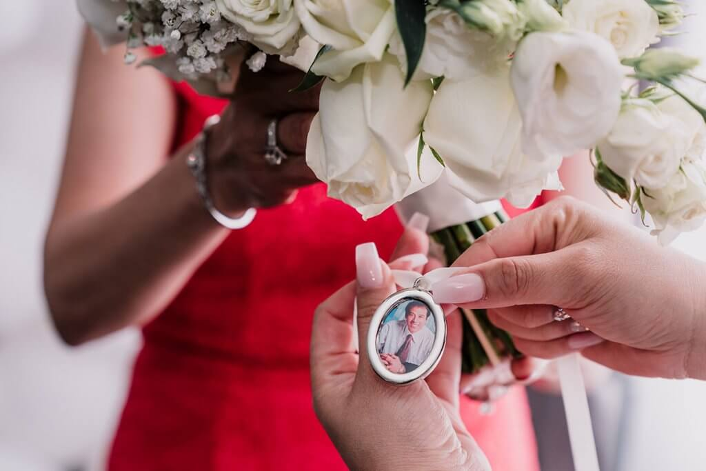 an image of bride's father inside a locket wrapped around her wedding bouquet