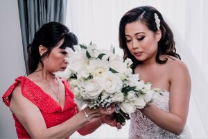 bride with her mom fixing a white roses bouquet