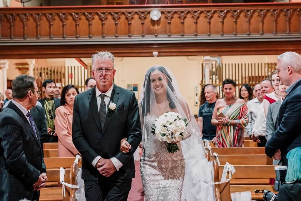 father walking his daughter down the aisle of St Brigid's Catholic Church