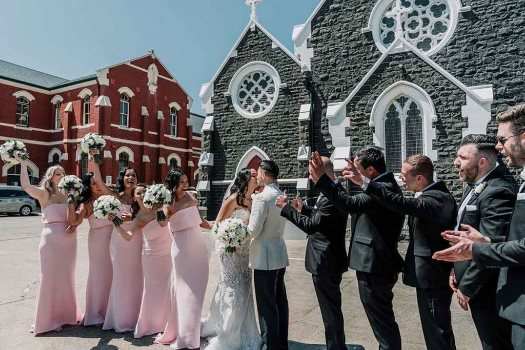 newly wed couple with bridal entourage in elegant church wedding in St Brigid's Catholic Church