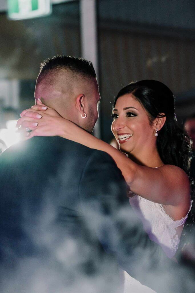 bride and groom looking at each other while doing the first dance
