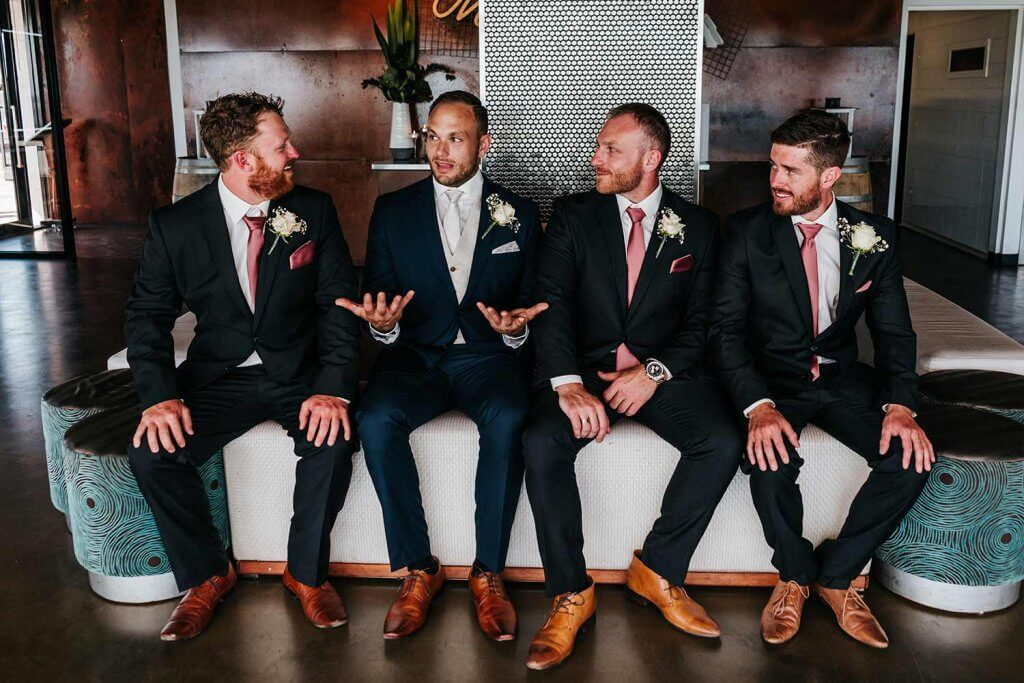 Groomsmen talking with each other in suits