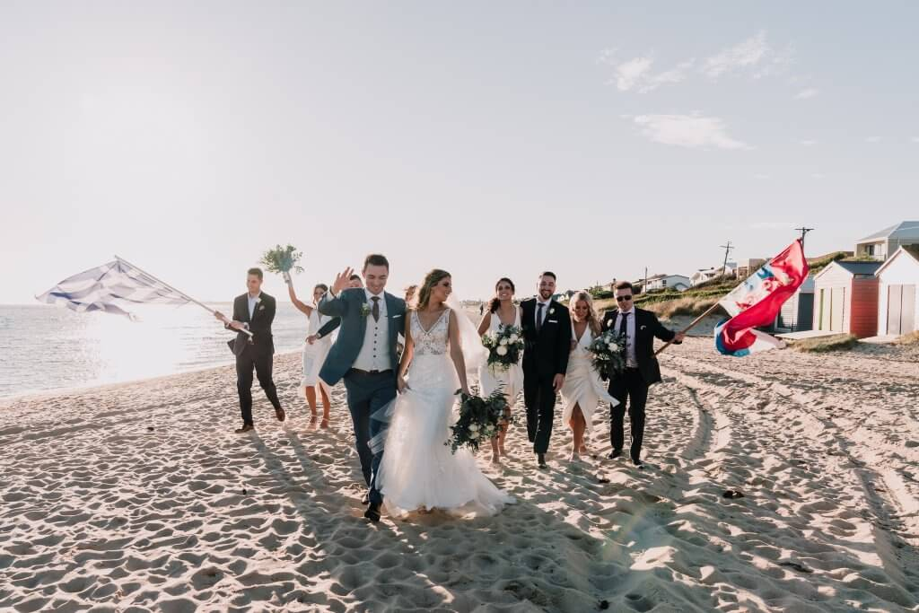Newlyweds walking by the beach with their groomsmen and bridesmaids