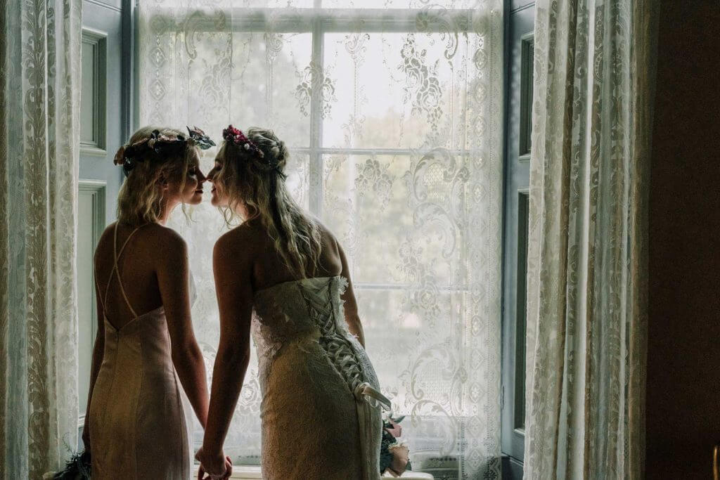 same sex lesbian couple Mrs and Mrs kissing at Overnewton Castle Melbourne captured by photographer Lowina Blackman from Black Avenue Productions